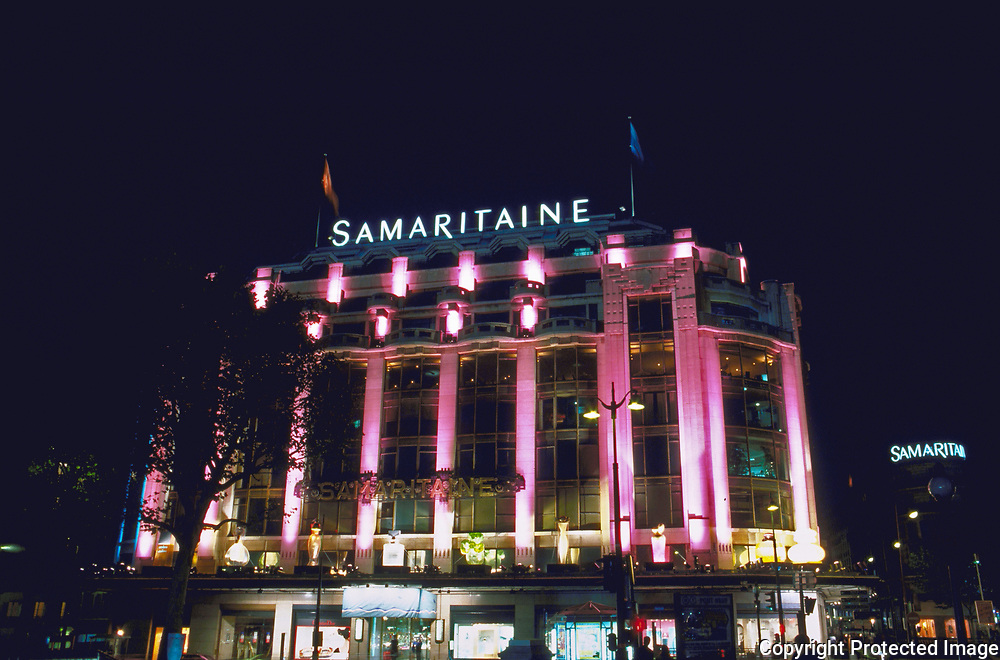 A Paris icon the Le Samaritaine department store lit at night by colored nights and illuminated giant bottles of perfume.
