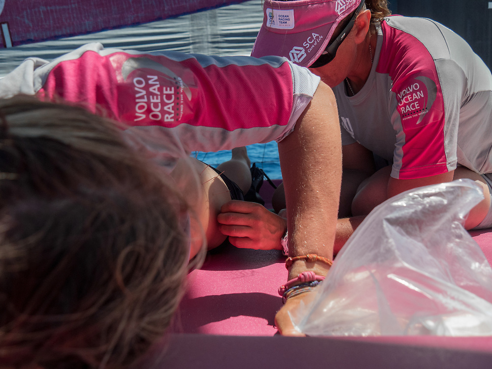"""December 04, 2014. Leg 2 onboard Team SCA. Dee Caffari """"dry needles"""" Sophie Ciszek to help Sophie's back which has started to cause her some trouble.punt"""