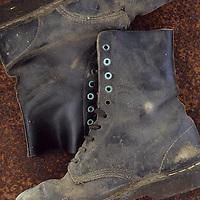Pair of well-worn black heavy-duty industrial working boots lying on rusty metal sheet