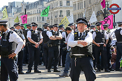 © Licensed to London News Pictures. 19/04/2019. London, UK. A large number of police presence around the pink boat in Oxford Circus on the fifth day of the climate change protest by the Extinction Rebellion movement group as they start to un-bond and arrest the activist. Photo credit: Dinendra Haria/LNP