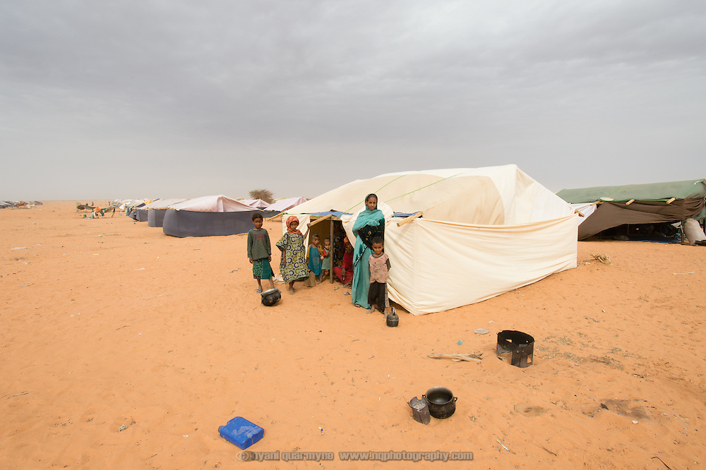 A family in the the newest section of the Mbera refugee camp for Malian refugees in Mauritania. As of 2 March 2013 this sections of the camp had no water points and no latrines. In addition, many families had been allocated tent locations, but have not received proper tents - in many cases the tent frames were covered with makeshift fabric, or families were staying with friends or relatives while they awaited the arrival of their tents.