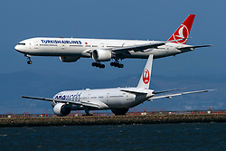 Boeing 777-3F2(ER) (TC-JJI) operated by Turkish Airlines landing past Boeing 777-346(ER) (JA732J) operated by Japan Airlines with the Oneworld livery at San Francisco International Airport (KSFO), San Francisco, California, United States of America