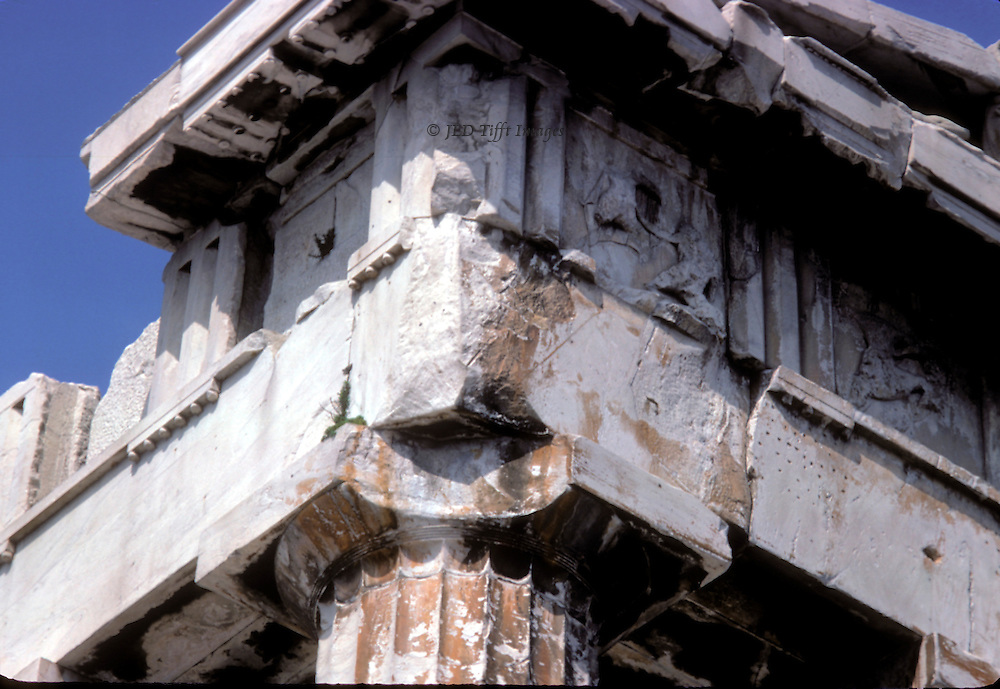 Acropolis: Parthenon, details of entablature, looking upward at one corner showing a piece of a column capital broken off and a gaping space along one cornice.