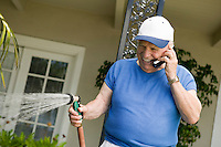 Senior Man Watering Yard and Using Cell Phone