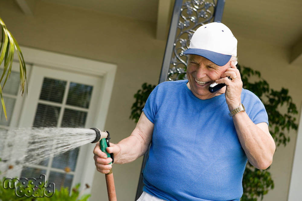 Senior Man Watering Yard and Using Cell Phone