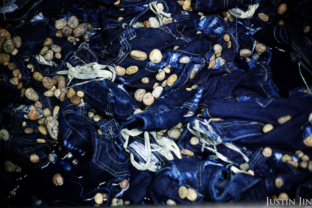 "Pumice stones are used to wash jeans in Zhongshan city, China, to give the ""stone-wash"" look. .This picture is part of a photo and text story on blue jeans production in China by Justin Jin. .China, the ""factory of the world"", is now also the major producer for blue jeans. To meet production demand, thousands of workers sweat through the night scrubbing, spraying and tearing trousers to create their rugged look. .At dawn, workers bundle the garment off to another factory for packaging and shipping around the world..The workers are among the 200 million migrant labourers criss-crossing China.looking for a better life, at the same time building their country into a.mighty industrial power."