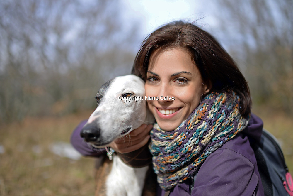 Exterior portrait of young woman with greyhound dog