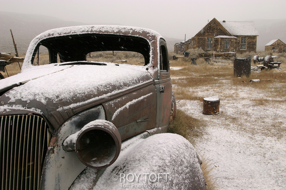 A dilapidated vehicle is parked in front of an abandoned building.
