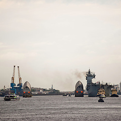 London, UK - 13 July 2012: Royal Navy's biggest ship HMS Ocean squeezes through Thames barriers towards Greenwich where it will be deployed as part of the security plan for the Olympic Games.