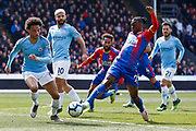 Crystal Palace defender Aaron Wan-Bissaka (29) at full stretch attempting to tackle Manchester City midfielder Leroy Sane (19) during the Premier League match between Crystal Palace and Manchester City at Selhurst Park, London, England on 14 April 2019.