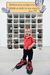 "© Licensed to London News Pictures. 27/09/2018. LONDON, UK. Emlyn Simmonds, aged two and a half, from Lewisham, wears a pair of size 13 shoes, in front of an installation called ""Walk A Mile In My Shoes"", 2006, by Bedwyr Williams  Preview of ""Black Mirror"", a major new exhibition featuring the work of 26 contemporary artists, at the Saatchi Gallery.  The show explores art's role in social satire and how political uncertainty has influenced art of recent years and runs 28 September to 13 January 2019.   Photo credit: Stephen Chung/LNP"