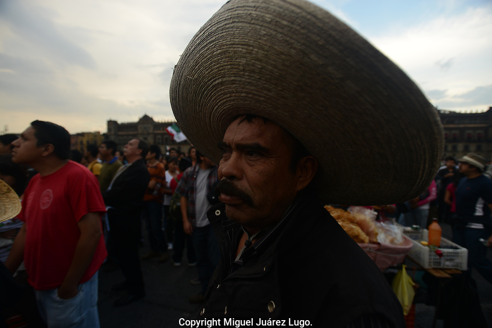 """Mexico City - A farmer listens to speeches during a demonstration billed as a """"Protest against the Imposition"""" of PRI's Enrique Peña Nieto as Mexico's next president. (PHOTO: MIGUEL JUAREZ LUGO)"""