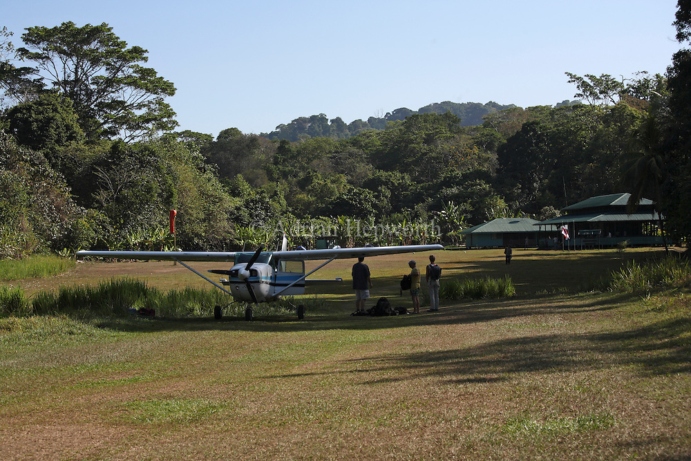 Airplane on landing strip at Sirena Ranger Station, Corcovado National Park, Osa Peninsula, Costa Rica. <br />
