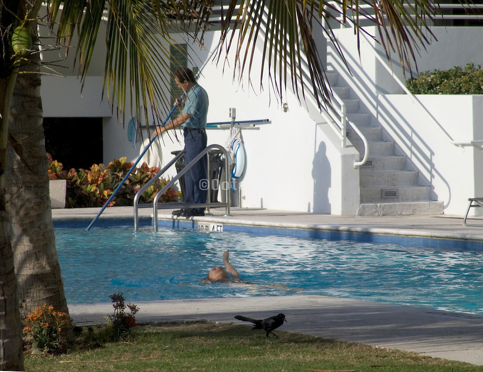 Woman swimming while man cleans the pool.