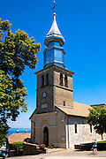 Tourist photographs Saint Pancrace d'Yvoire church in the old district of Yvoire by Lac Leman, Lake Geneva, France