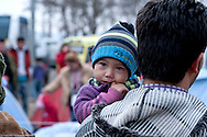 Afghan child named Sara in her father's arms in line to eat, while on their way with a bus from Athens to Idomeni village at the Greek - Macedonian border, 8 Febraury 2016. Hundreds of refugees  wait every day at a gas station used as a temporary camp outside of Polykastro city at the north part of Greece until they receive the order from the police to move to the Greece- Macedonian border and continue their trip  to North Europe.