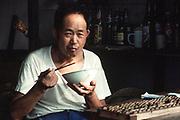 Man eating with chopsticks, Guangzchou, China