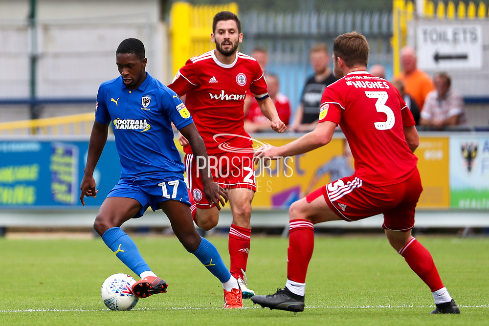 AFC Wimbledon attacker Michael Folivi (17) dribbling and battles for possession with Accrington Stanley defender Mark Hughes (3) during the EFL Sky Bet League 1 match between AFC Wimbledon and Accrington Stanley at the Cherry Red Records Stadium, Kingston, England on 17 August 2019.