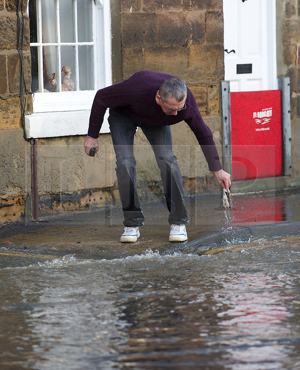 © Licensed to London News Pictures. 27/01/2013..Cleveland, England, UK..Following the recent snowfall a fast thaw through the night brought heavy flooding to some parts of Cleveland and North Yorkshire with many roads closed...A man tries to clear a blockage from the drain outside his house to let flood water escape in Loftus in Cleveland...Photo credit : Ian Forsyth/LNP