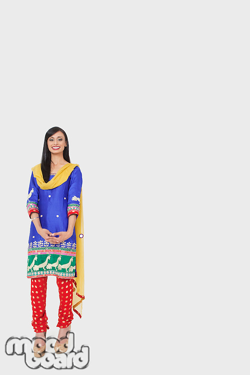 Full length portrait of Indian woman in traditional wear standing over gray background