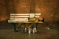 A man sleeping on a bench. During summer nights, on Changan jie, near Tian An Men square, the benches are occupied by tourists, homeless, migrant-workers who spend the night there waiting for the sun to rise.