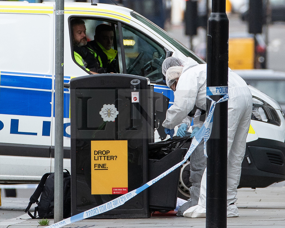 © Licensed to London News Pictures. 11/10/2019. Manchester, UK. Forensic scenes of crime examiners search through a bin on Exchange Square at the foot of the steps to the Arndale Centre . Terrorism Police are investigating after four people were stabbed during a single attack at the Arndale Centre in Manchester City Centre . Photo credit: Joel Goodman/LNP