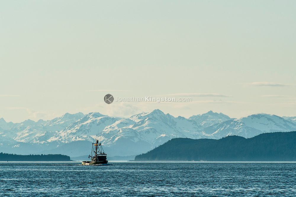 Commercial fishing boat on the ocean with snow capped mountains.