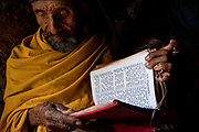 "Gazgibla, Ethiopia - 18.05.17  - Kibret, 78, who had trachoma in his left eye, reads a book in Gazgibla, Amhara Region, Ethiopia, on May 18, 2017. ""I was a priest, but due to the vision problems, I couldn't read my books."" He also experienced strong headaches with his low vision before receiving CBM-sponsored trichiasis surgery.  ""After the surgery, I felt relief. I thank God for the donor."""