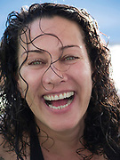 Portrait of a Happy smiling woman in her 40s with wet hair after a dip in the pool during a summer holiday - Model Release Available