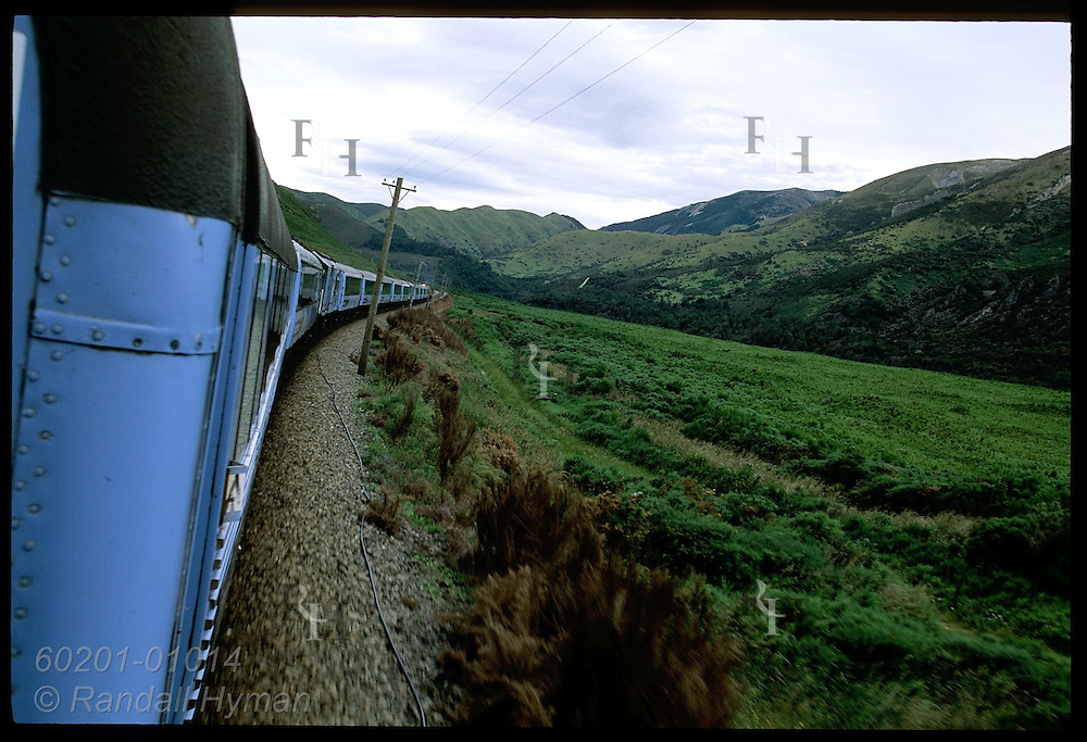 TranzAlpine Express train rounds curve in Southern Alps as it speeds from Christchurch to Greymouth; New Zealand.