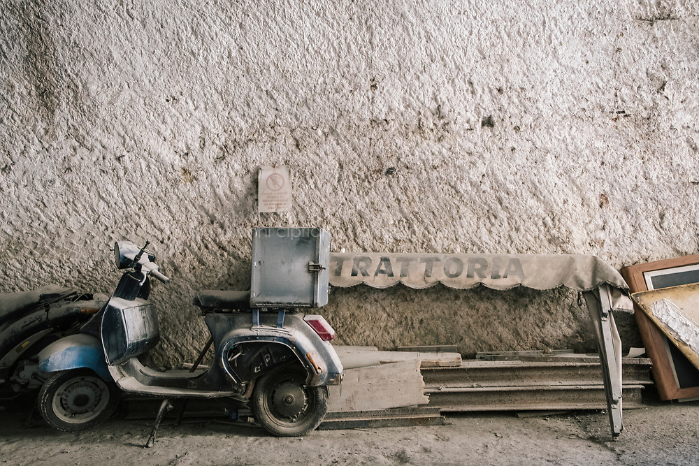 NAPLES, ITALY - 1 AUGUST 2018: A scooter is parked in the garage of Cantina del Gallo, a family-owned restaurant in the Rione Sanità in Naples, Italy, on August 1st 2018. The garage is located inside a huge cave dug into the soft tufa stone. First excavated by the Romans, this now urban grotto was used in the Second World War as a shelter during aerial bombings.<br /> <br /> Cantina del Gallo, in the Rione Sanità, was established in 1898 and run by four generations of the Silvestri family. The cantina began as a store selling bulk wine and oil. It was only in the 1950s, when the legendary Aunt Cuncetta began cooking, that it became the simple and genuine tavern it is today.<br /> There are three dishes that are the restaurant's workhorses, and the ones we always seem to rotate between: the pennette alla sorrentina (a variation of the classic gnocchi alla sorrentina, seasoned with tomato, basil and stringy mozzarella), the baked cod (although the fried cod is just as mouth-watering) and the pizza cafona (peasant pizza), topped with oregano, cheese, chile and with double the tomatoes (tomato juice and chopped tomatoes).