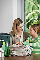 Woman and girl preparing waste paper for recycling smiling