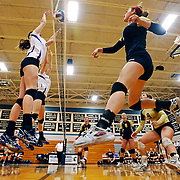 Kris Wilson/News Tribune.Helias outside hitter Tory Wiley records the kill after drilling a shot off the hands of a pair of Camdenton blockers during Monday night's matchup at Rackers Fieldhouse.