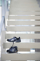 Pair of untied athletic shoes on stairs