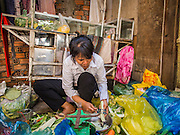 24 FEBRUARY 2015 - PHNOM PENH, CAMBODIA: A woman who lives in the White Building cleans vegetables to sell. The White Building, the first modern apartment building in Phnom Penh, originally had 468 apartments, and was opened the early 1960s. The project was overseen by Vann Molyvann, the first Cambodian architect educated in France. The building was abandoned during the Khmer Rouge occupation. After the Khmer Rouge were expelled from Phnom Penh in 1979, artists and dancers moved into the White Building. Now about 2,500 people, mostly urban and working poor, live in the building. Ownership of the building is in dispute. No single entity owns the building, some units are owned by their occupants, others units are owned by companies who lease out apartments. Many of the original apartments have been subdivided since the building opened and serve as homes to two or three families. The building has not been renovated since the early 1970s and is in disrepair. Phnom Penh officials have tried to evict the tenants and demolish the building but residents refuse to move out.   PHOTO BY JACK KURTZ