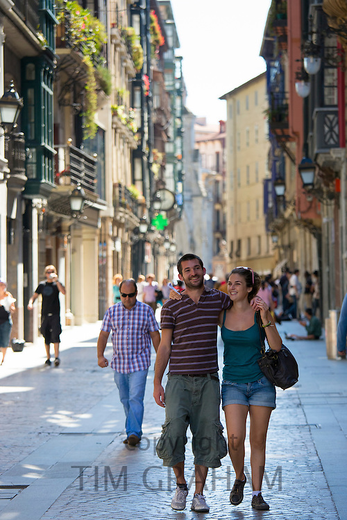 Young couple stroll arm in arm in Calle de Bidebarrieta in Bilbao, Spain