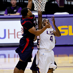 November 23, 2011; Baton Rouge, LA; LSU Tigers guard Chris Bass (4) shoots over South Alabama Jaguars center Augustine Rubit (21) during overtime of a game at the Pete Maravich Assembly Center. South Alabama defeated LSU in overtime 79-75. Mandatory Credit: Derick E. Hingle-US PRESSWIRE