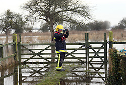 © London News Pictures. 31/01/2014. Burrowbridge, UK. A fireman examining flood waters in Burrowbridge, Somerset on the Somerset levels.  The area has been hit severely by recent flooding which is forecast to get worse over the weekend . Photo credit: Jason Bryant/LNP
