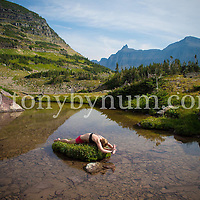 woman doing yoga in mountains on small island in alpine mountain lake