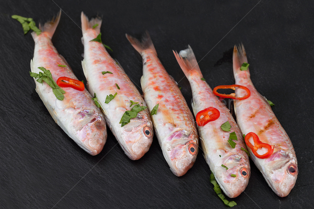 Raw red mullet fish seasoned with chopped parsley and red pepper, on black background.