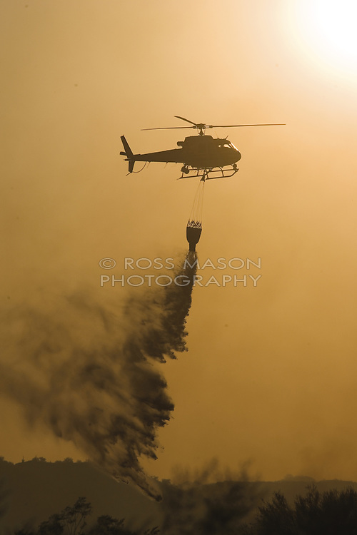 Helicopter dumps water on Desert Hills fire.