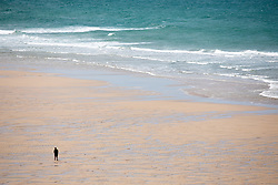 "© Licensed to London News Pictures. 11/05/2020. Newquay, UK. A man walks along Watergate Bay beach on the North coast of Cornwall, the day after British Prime Minister Boris Johnson announced a 'road map' to lift lockdown restrictions due to Covid-19, (Coronavirus). A rise in ""staycations"" - the concept of holidaying in your home country rather than travelling abroad - is expected, with many visitors planning to visit Cornwall. However, an ongoing campaign titled ""#ComeBackLater"" is trying to persuade tourists not to visit the county until it is safe to do so. Photo credit : Tom Nicholson/LNP"