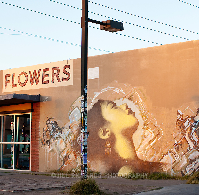 Art mural collaboration between El Mac and Augustine Kofie is probably the most well known mural in Phoenix. It is located on the side of what was formerly Pravus Gallery after they debuted their last show in May on First Friday. The building was originally a flower shop built in the 1950?s, hence the old signage that still stands today.