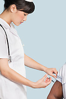 Female nurse injecting patient's arm over light blue background
