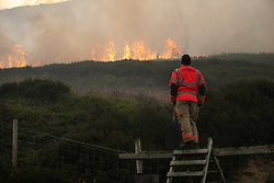 "© Licensed to London News Pictures . 27/06/2018 . Saddleworth , UK . Homes are evacuated and a Major Incident is declared as fire-fighters work to control large wildfires spreading across Saddleworth Moor and towards residential areas in surrounding towns . Very high temperatures , winds and dry peat are hampering efforts to contain the fire , described as "" unprecedented "" by police and reported to be the largest in living memory . Photo credit : Joel Goodman/LNP"