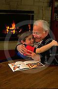 Grandson hugs grandfather at home with fireplace