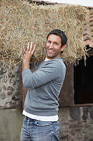 Man carrying hay on shoulders outdoors portrait