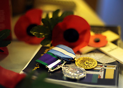 © Licensed to London News Pictures. 07/11/2011. Richmond, UK. Two medals on a workers desk. Red Poppies being made in The Poppy Factory in preparation for sale in 2012, Richmond, Surrey today 7th November.  The factory has been supplying the poppy, crosses and wreathes to the British Legion for almost 90 years. It is staffed by veterans, many whom of which are injured, sick or wounded of all ages. Photo credit : Stephen Simpson/LNP