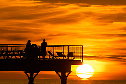 ©Licensed to London News Pictures. 18/09/2019 Aberystwyth UK. <br /> The sun setting gloriously over  Cardigan Bay silhouettes people on the seaside pier at the end of a day of unbroken clear blue skies and warm September sunshine in Aberystwyth ,  as the 'indian summer' mini heat-wave continues over much of the souther parts of the UK. Photo credit Keith Morris/LNP