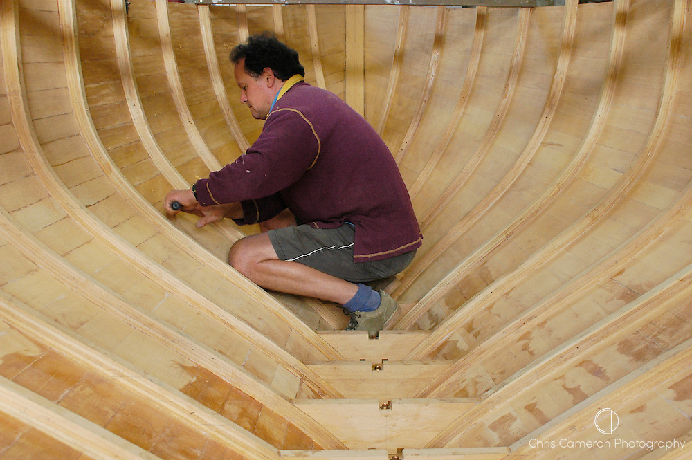 Herbert Krumm-Gartner at work in the hull of the 26 ft. Pilot Sloop designed by American naval architect George Stadel in 1939, he is biulding at his Classic Boats Ltd workshop outside Auckland. 7/5/04  (© 2004 Chris Cameron)